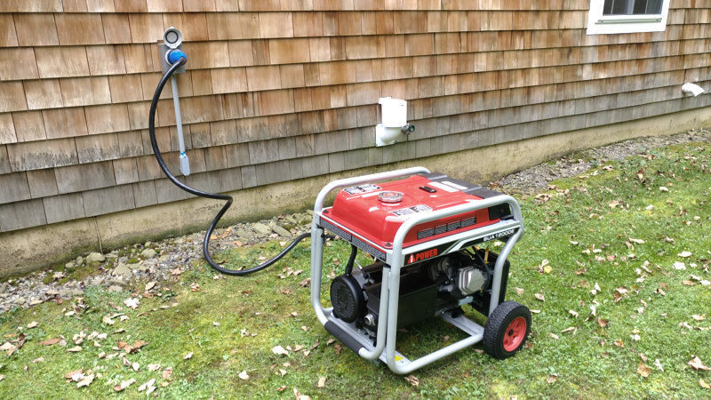 Portable generator in the grass outside the author's home and connected to the house using a generator cable